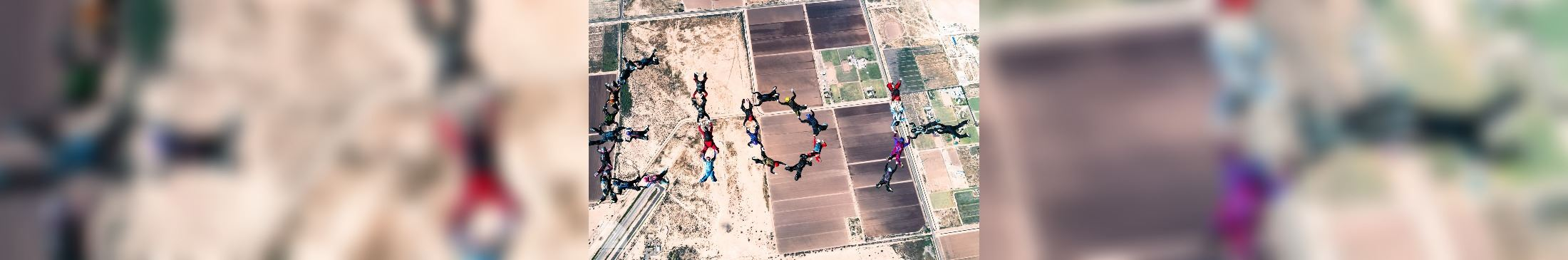 Skydivers linking hands to spell ELOY